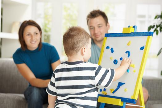 niño-jugando-pizarra-magnetica-mientras-padres-lo-miran.jpg