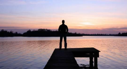 Man-standing-alone-pink-sunset