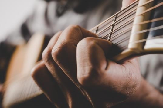 primer-plano-de-la-mano-del-hombre-tocando-la-guitarra_1150-1466