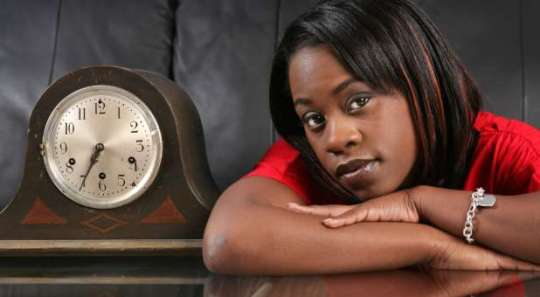 african american girl waiting for her date next to an antique clock