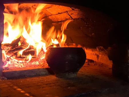 81599774-olla-de-hierro-fundido-con-agua-dentro-de-la-estufa-rusa-llama-de-fuego-leña-y-brasas-forma-tradicional.jpg